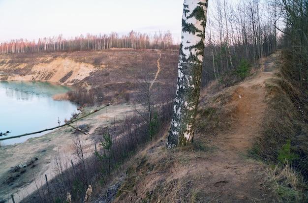 Na szczycie wzgórza znajduje się ścieżka między drzewami na brzegu kamieniołomu piasku.