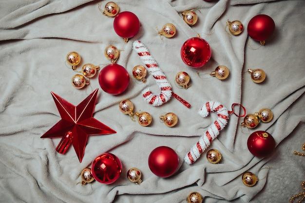 Na szkockiej kracie leżały płaskie czerwone bombki, złote bombki, czerwona gwiazda i świąteczne laski z cukierkami.