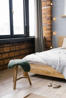Na taborecie przy łóżku leży zielony koc, stojąc. blisko okna. dom skandynawski