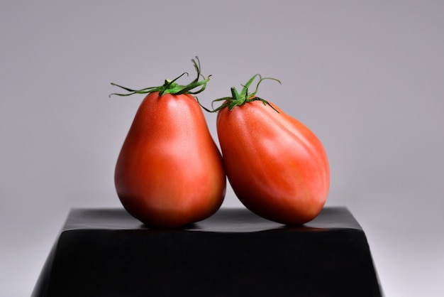 Na tacy dwa czerwone dojrzałe pomidory z luksusowym czarnym tłem