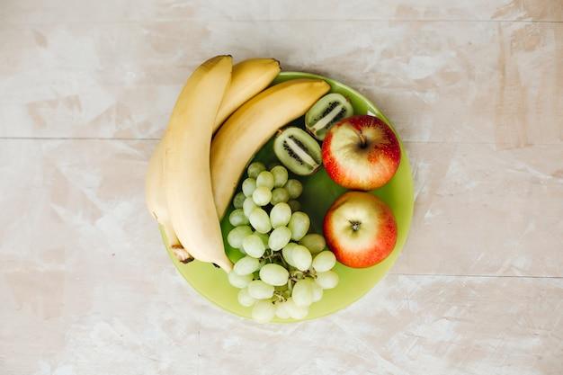 Na talerzu całe świeże warzywa: sałata, ogórki, pomidory, marchewka. sałata i świeże warzywa z bliska. skład z surowymi warzywami.