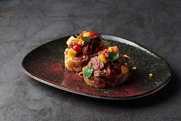 Na talerzu leżą dwa brusquette z warzywami i mięsem