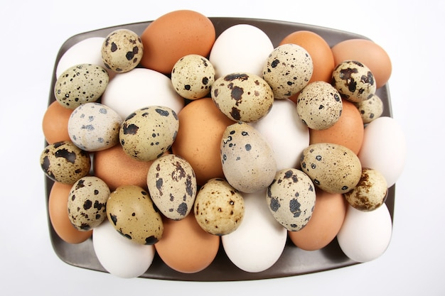 Na talerzu leżą różne jaja przepiórcze i kurze