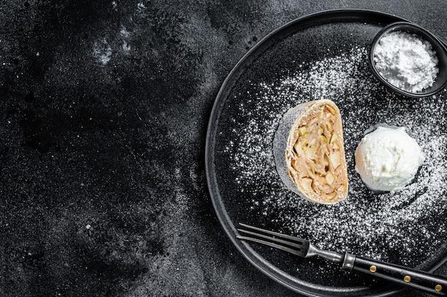 Na talerzu strudel jabłkowy z cynamonem, cukrem pudrem i lodami waniliowymi