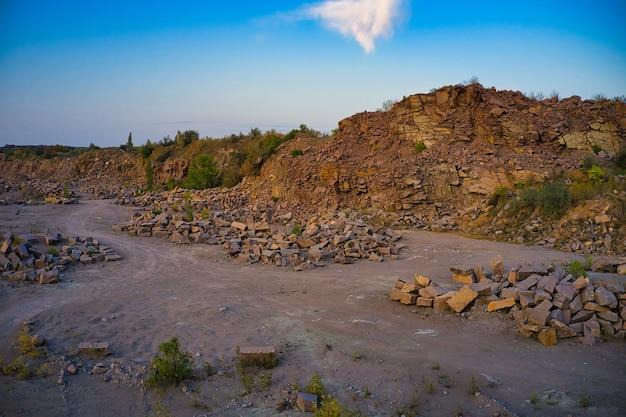 Na terenie starego zalanego kamieniołomu w ciepłym wieczornym świetle znajdują się duże stosy głazów.