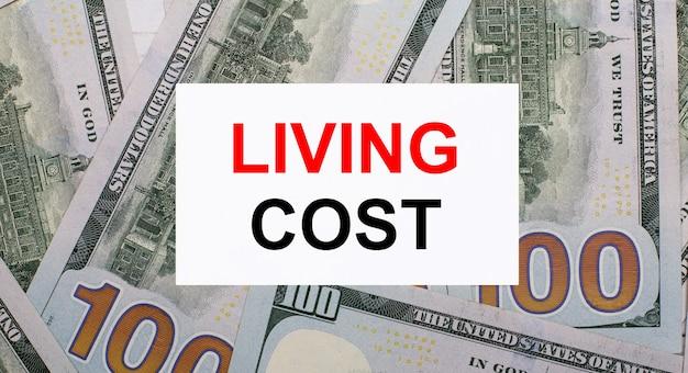 Na tle dolarów amerykańskich biała kartka z napisem living cost. koncepcja finansowa