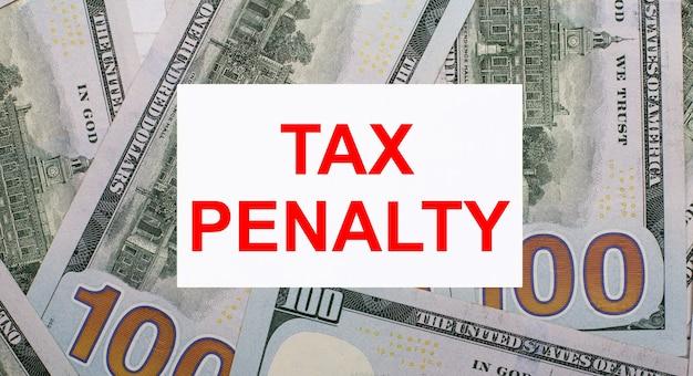 Na tle dolarów amerykańskich biała kartka z tekstem kara podatkowa. koncepcja finansowa
