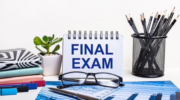 Na tle niebieskiego schematu i białej ściany, czarne ołówki w stojaku, kwiatek, pamiętniki i zeszyt z napisem final exam