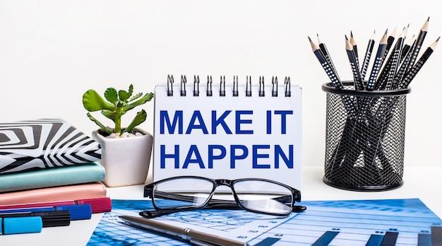 Na tle niebieskiego schematu i białej ściany, czarne ołówki w stojaku, kwiatek, pamiętniki i zeszyt z napisem make it happen
