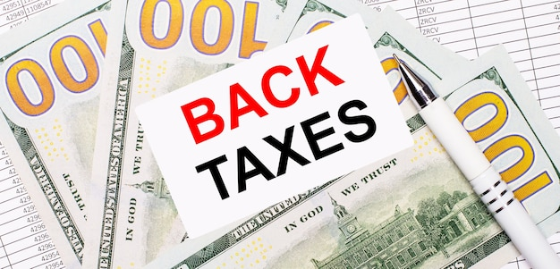 Na tle raportów i dolarów - biały długopis i karteczka z napisem podatki zwrotne