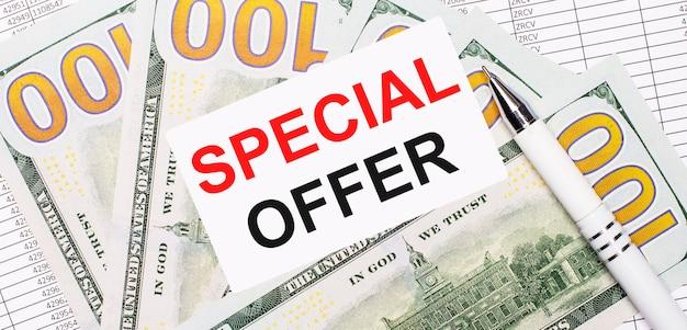 Na tle raportów i dolarów - biały długopis i kartka z napisem oferta specjalna. pomysł na biznes