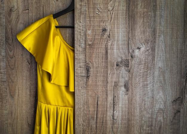 Na tle szafy wisi żółta sukienka.