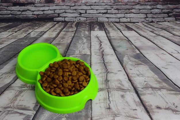 Na tle szarych desek leży zielony plastikowy talerz wypełniony suchą karmą na karmę