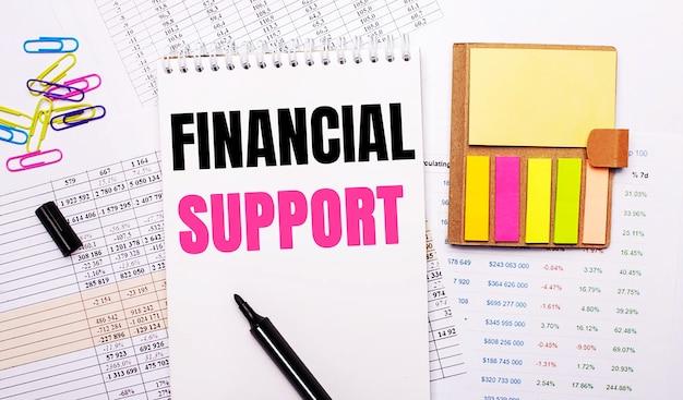 Na tle wykresów leży notes z napisem financial support, marker, kolorowe spinacze i jasny papier notesowy