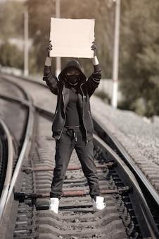 Na torach stoi młoda protestantka, trzymająca plakat z napisem nad nią