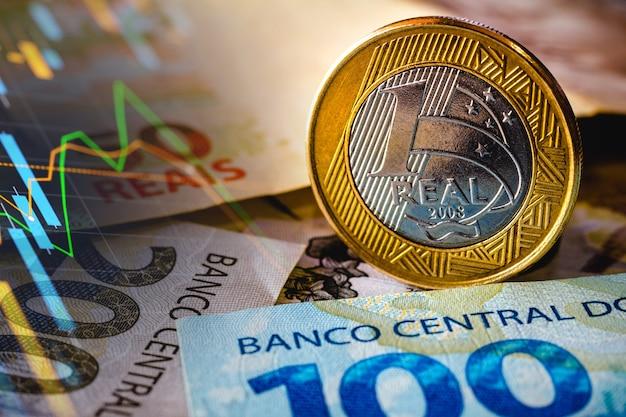 Na tym zdjęciu wyświetlana jest ilustracja pięćdziesięciu stu dwustu realiów i podświetlona moneta jednorealowa real to bieżące pieniądze w brazylii