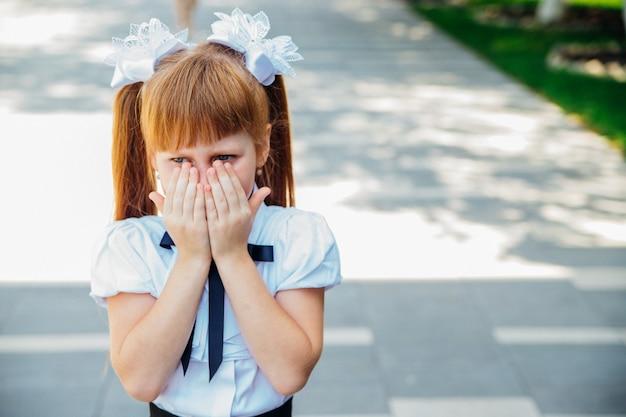 Na ulicy stoi mała dziewczynka, uczennica szkoły podstawowej. dziewczyna zakrywa twarz rękami.