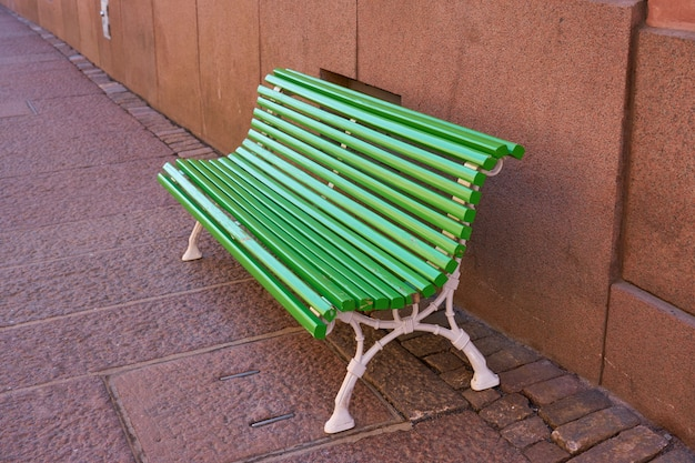 Na ulicy zielona drewniana malowana ławka.