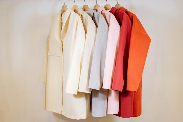 Na wieszakach wymieszać rząd kolorowych płaszczy damskich