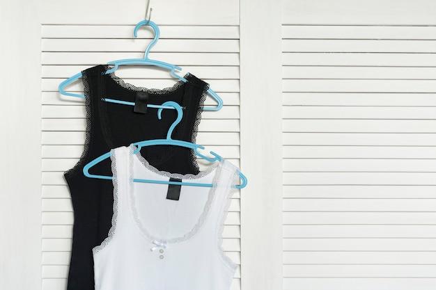 Na wieszaku koszulki w kolorze biało-czarnym. białe okiennice w tle