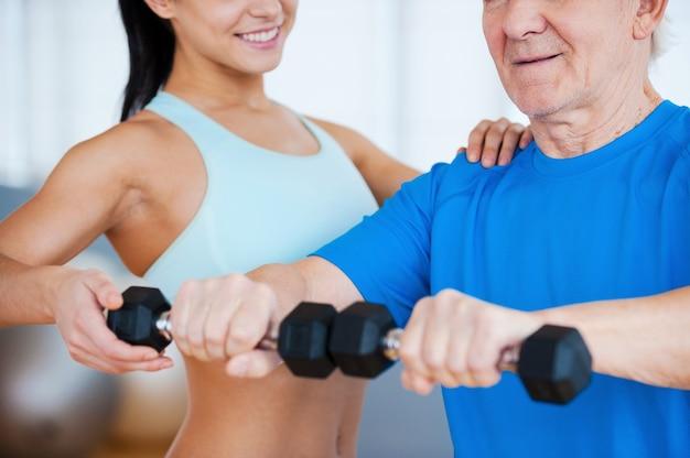 Na właściwej drodze do wyzdrowienia. przycięty obraz fizjoterapeutki pomaga starszemu mężczyźnie w fitness w klubie fitness
