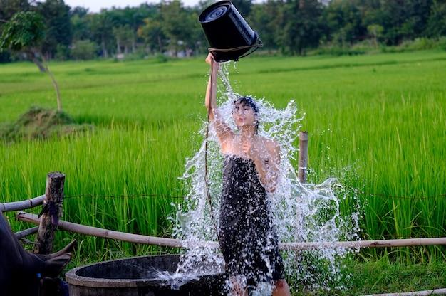 Na wsi wiejska dziewczyna bierze prysznic z tradycyjnego źródła wód gruntowych.