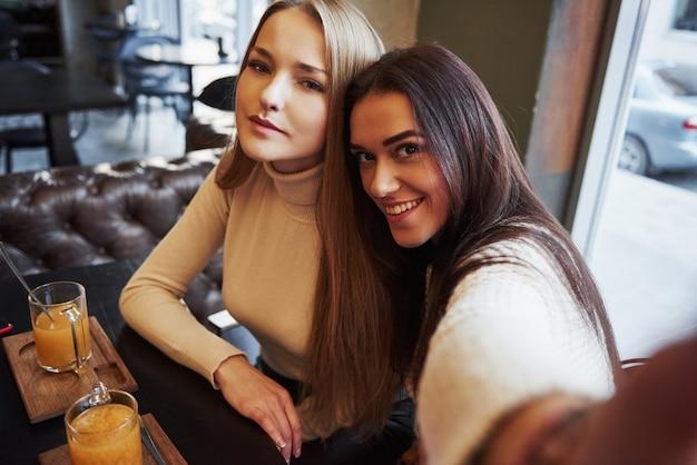 Na wydłużonej dłoni. młode koleżanki biorą selfie w restauracji z dwoma żółtymi napojami na stole