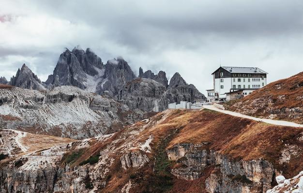 Na wzgórzach. budynek stojący wysoko w górach w pobliżu kilku klifów z mgłą i chmurami.