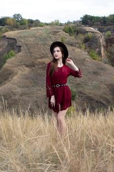 Na wzgórzach stoi piękna kobieta z długimi włosami w kapeluszu i bordowej sukience