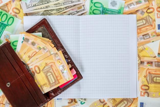 Na zbiorze banknotów 100 euro, 50 euro i 100 dolarów leżał biały zeszyt z pustymi stronami.