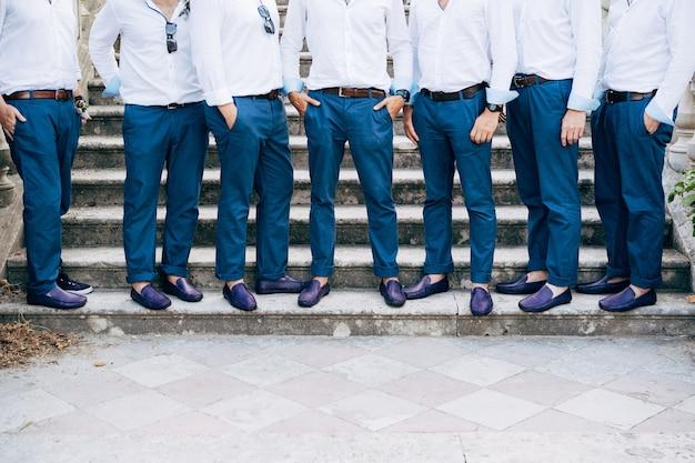 Na zbliżeniu schodów stoi siedmiu drużbów w identycznych niebieskich spodniach i butach