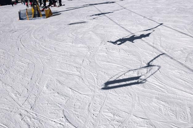 Na zboczu góry wyświetlane są cienie narciarzy wchodzących na wyciąg narciarski
