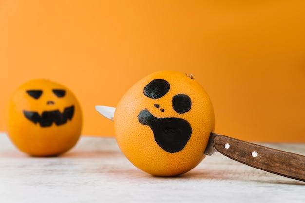 Na zdjęciu cytrusy z nożem w środku i innym pomarańczowym na tle