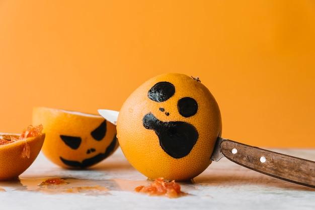 Na zdjęciu owoce z nożem przebijającym i pomarańczowym halloween z tyłu