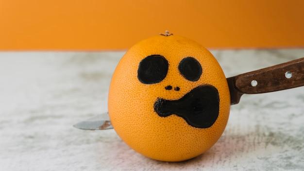 Na zdjęciu twarz na owocu z przebitym nożem w środku