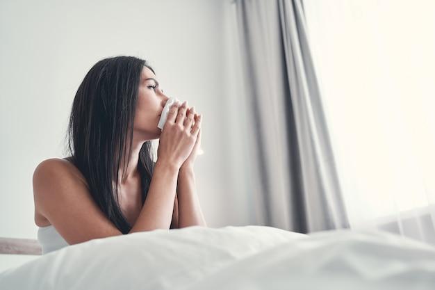Na zdrowie. zdenerwowana brunetka siedzi w ciepłym łóżku i wyciera nos