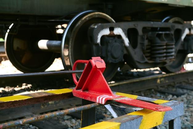 Na zębatce leży czerwona szczęka hamulca kolejowego.