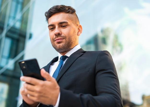 Na zewnątrz biznes człowiek sukcesu patrząc na telefon