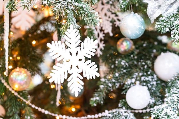 Na zewnątrz choinka z białymi płatkami śniegu i dekoracją