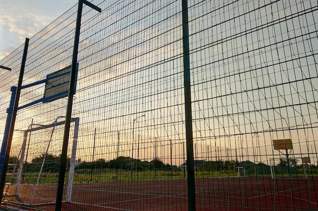 Na zewnątrz mini boisko do piłki nożnej i koszykówki z bramką i koszykiem otoczone wysokim ogrodzeniem ochronnym.