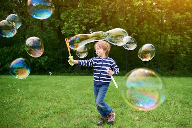 Na zewnątrz portret ładny chłopiec w wieku przedszkolnym dmuchanie baniek mydlanych