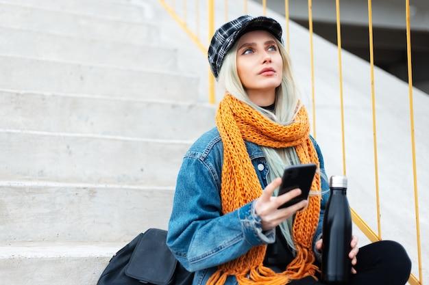 Na zewnątrz portret młodej dziewczyny blond podróżnika, patrząc w górę, za pomocą smartfona, trzymając stalową butelkę termiczną