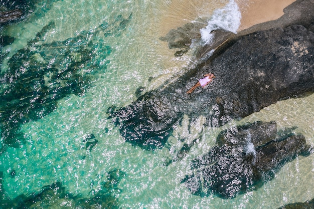 Na zewnątrz portret moda styl życia ładnej dziewczyny leżącej na dużych kamieniach w morzu. na sobie stylową krótką różową sukienkę. samotny. fotografia artystyczna twórczy. widok z góry