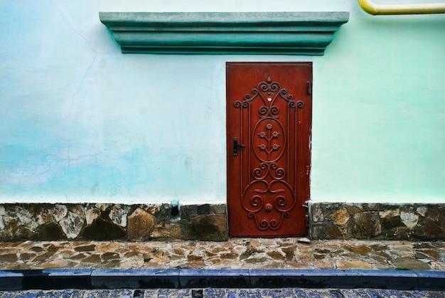 Na zewnątrz starego domu z częścią ulicy i drzwiami z kutego żelaza w mieście eupatoria bez okien