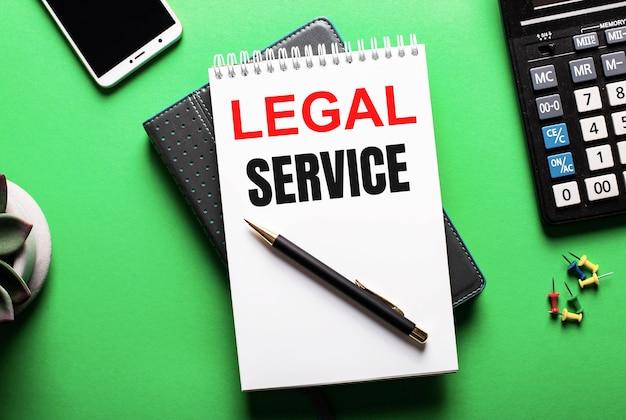 Na zielonej nawierzchni - telefon, kalkulator i pamiętnik z napisem legal service