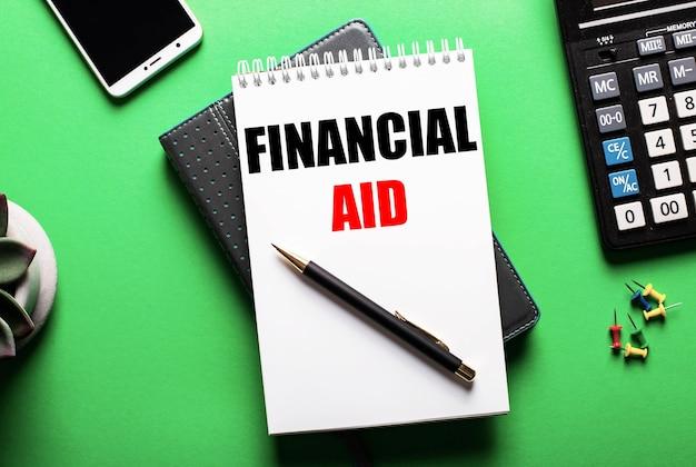 Na zielonej nawierzchni - telefon, kalkulator i pamiętnik z napisem pomoc finansowa