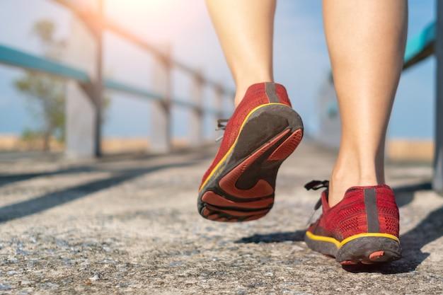 Na zielonym tle kobieta chodzi i biega w butach do biegania. ćwiczenia dla zdrowia to pojęcie.