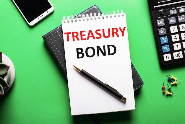 Na zielonym tle telefon, kalkulator i pamiętnik z napisem treasury bond