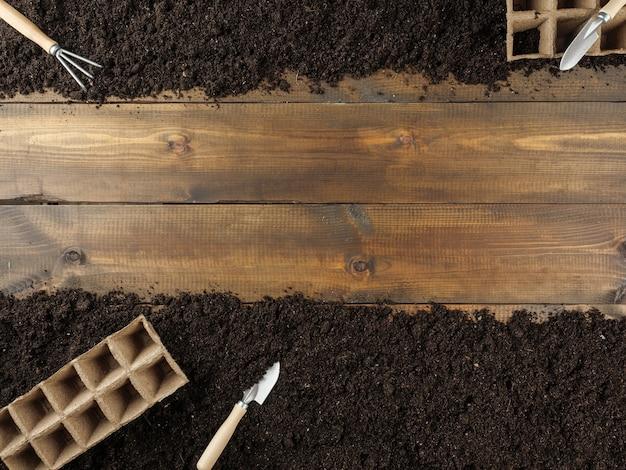 Na ziemi leżą doniczki z torfem i narzędzia ogrodnicze. na środku drewniane deski. skopiuj miejsce. widok z góry.