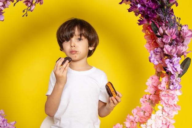 Na żółtej podłodze stał dziecięcy chłopiec w białej koszulce, jedzący pączki, siedzący na kwiatku